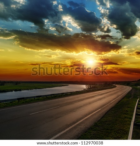 dramatic sunset over asphald road - stock photo