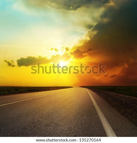 dramatic sunset over asphalt road - stock photo