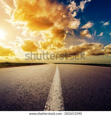 dramatic sunset over asphalt road - stock photo