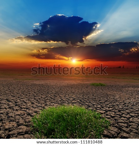 dramatic sunset over barren earth - stock photo