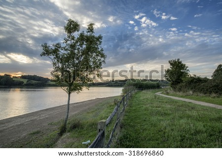 Dramatic sunset over calm lake in Summer in English countryside - stock photo