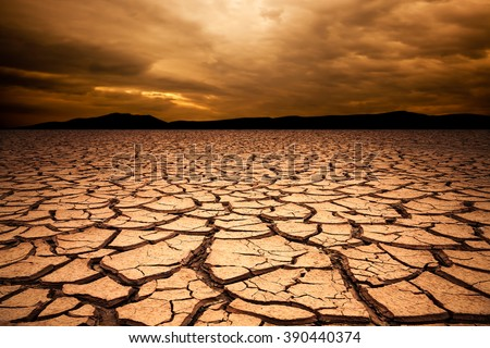 dramatic sunset over cracked earth. Desert landscape background. Global warming concept