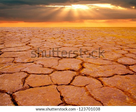 dramatic sunset over drought land - stock photo