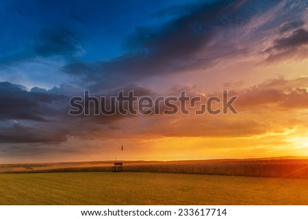 Dramatic sunset over fields with clouds during late summer - stock photo