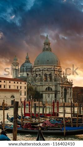 Dramatic sunset over Grand Canal and Basilica Santa Maria della Salute with gondolas in front, Venice, Italy - stock photo