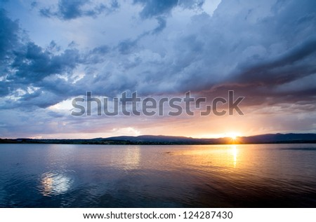 Dramatic sunset over quiet lake - stock photo