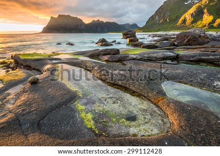 Dramatic sunset over Uttakleiv beach on Lofoten islands in Norway with a natural pond in the foreground. Hdr processed. - stock photo