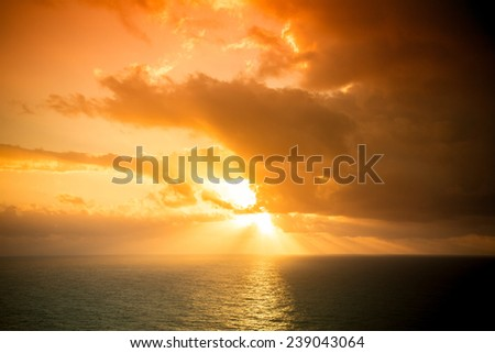 Dramatic sunset rays through a cloudy dark sky over the ocean. Tinted - stock photo