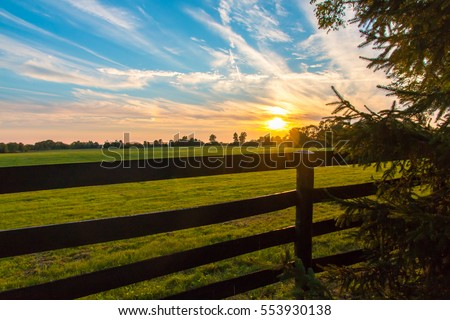 Dramatic sunset sky on countryside with lens flare.