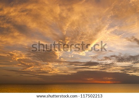 Dramatic sunset sky with clouds over ocean.