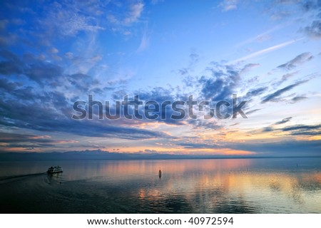Dramatic sunset sky with clouds over  the water - stock photo