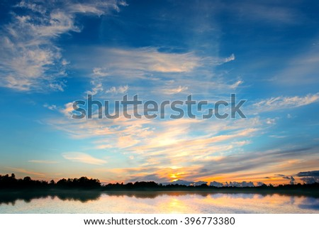 Dramatic sunset sky with forest lake and clouds