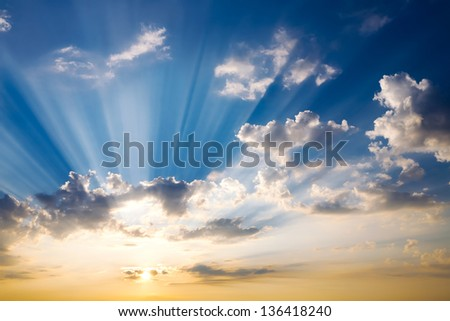 Dramatic sunset sky with sunbeam against clouds - stock photo