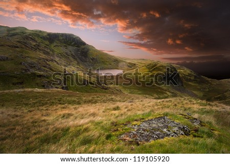 Dramatic sunset with beautiful sky over mountain range giving a strong moody landscape - stock photo