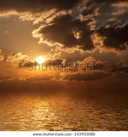 Dramatic sunset with clouds reflected in water. - stock photo