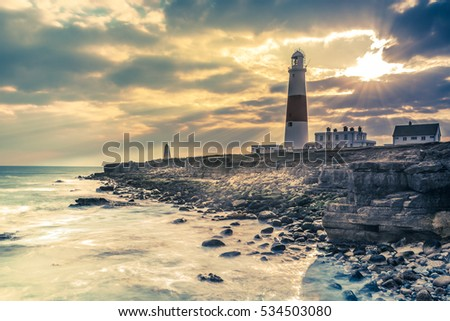 Dramatic sunset with iconic lighthouse on coast in Portland, UK.
