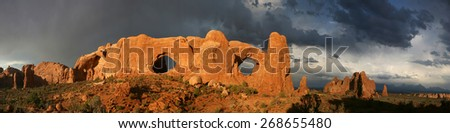 Dramatic sunset with storm clouds in background - Arches National Park  Windows section in Moab Utah USA - stock photo