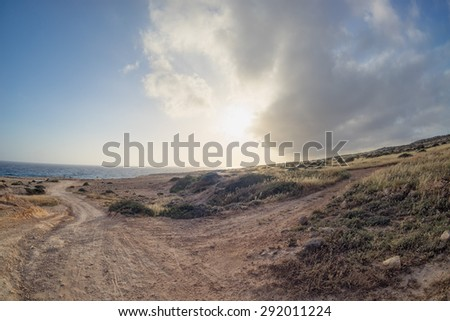 Dramatic sunset with storm cloudscape over Mediterranean Sea coastline fisheye view at sunset. Cape Greko, Cyprus.  - stock photo