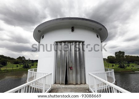 Dramatic swirling storm clouds above a reservoir pump tower.