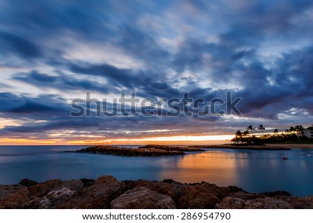 Dramatic tropical beach sunset with palm trees in Oahu, Hawaii - stock photo