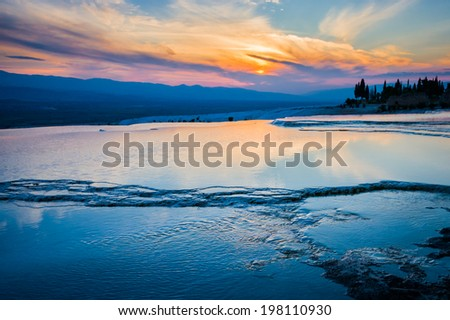 Dramatic turquoise pools in Pamukkale at sunset - stock photo