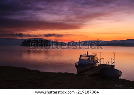 Dramatic unique red sunrise over the lake and small calm dock and boat - stock photo