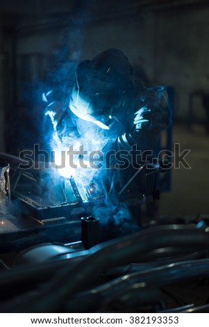 dramatic view of a worker wearing protective gear, welding together pieces of an exhaust pipe, with several other pipes around, on the work table, and metal blue frames in the background