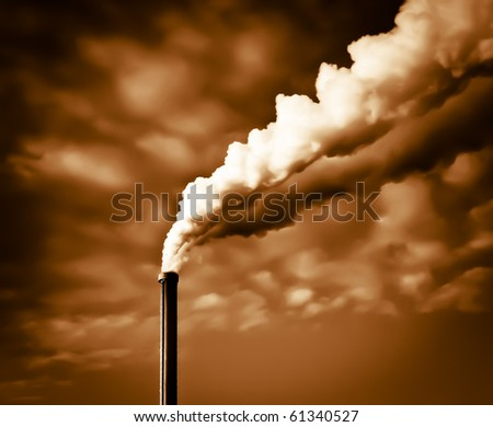 Dramatic view of an industrial chimney with exhalations of steam