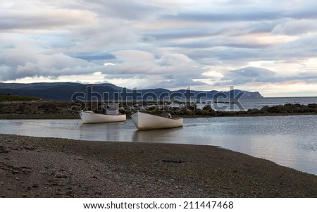Dramatic View of Two Boats at Sunset Rocky Harbor Gros Morne Park Newfoundland - stock photo