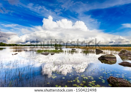 Dramatic white cloud over a bright blue lake on a sunny day - stock photo