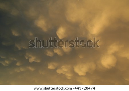Dramatic, yellow clouds in the sky after a thunderstorm during a summer evening. - stock photo