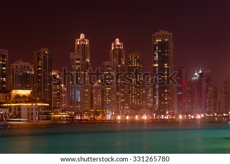 Dramatically lit nighttime skyline of a major metropolitan city, standing over a beautiful, tropical sea.