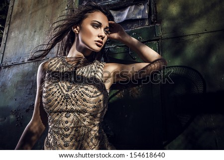 Dramatized image of sensual & attractive young woman in luxury dress posing outdoors. - stock photo