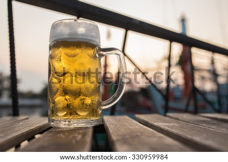 Draught Beer with fisherman boat backgroung in the evening time (Selective focus point) - stock photo