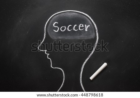 Draw the shape of a human head on the blackboard ( soccer in the brain ) - stock photo