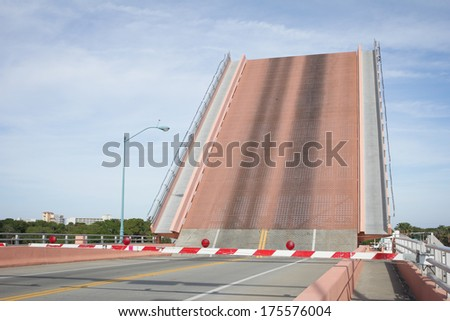 DRAWBRIDGE Drawbridge raises on road over river to allow boats to pass.