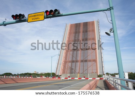 Drawbridge raises on road over river to allow boats to pass. - stock photo