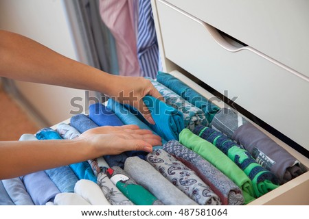 Drawer with t-shirts in the closet. Men's Clothing lying in the locker room. The order in the men's wardrobe.