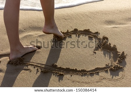 drawing an heart on the sand - stock photo
