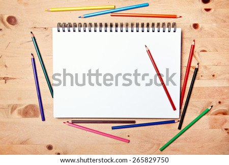 drawing block with copy space on wood table with colored pencil - stock photo