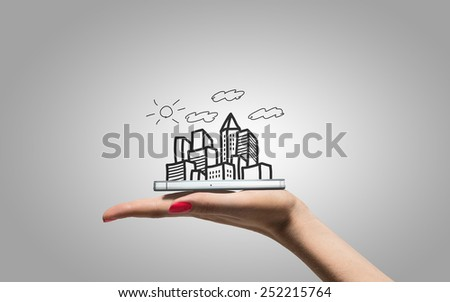 Drawing city skyscrapers on hand with smartphone - stock photo