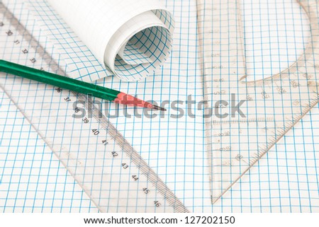 drawing compass and ruler on table with grid sheet