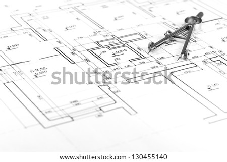 Drawing compass on architectural blueprints - stock photo