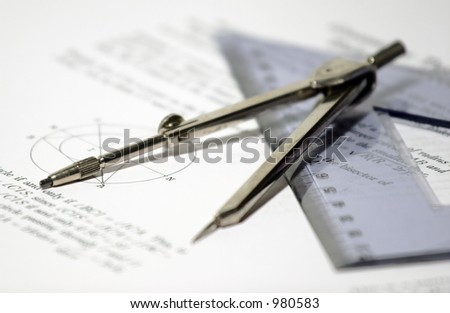 Drawing compass, triangle and geometric papers - selective focus - stock photo