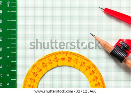 Drawing Compasses and Ruler on green graph paper with copy space - stock photo