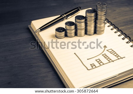 Drawing growth graph in notebook with heap coins stair, financial plan concept - stock photo