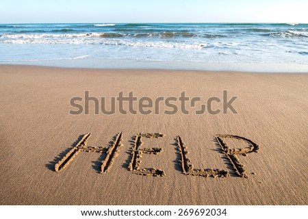 Drawing HELP on the sand - stock photo