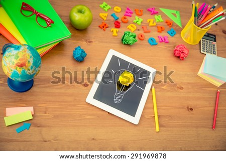 Drawing lamp bulb on tablet PC. School items on wooden desk in class. Education concept. Top view - stock photo