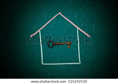 Drawing of a house and a vintage key on a green chalkboard - stock photo