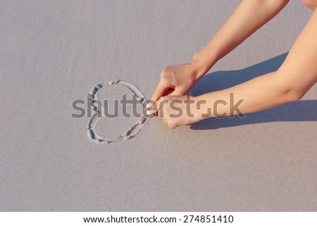 Drawing on white sand beach, heart symbol, hands - stock photo